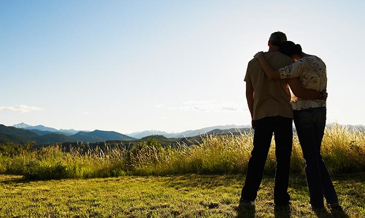 Couple holding each other with one arm watch sunrise on hilltop