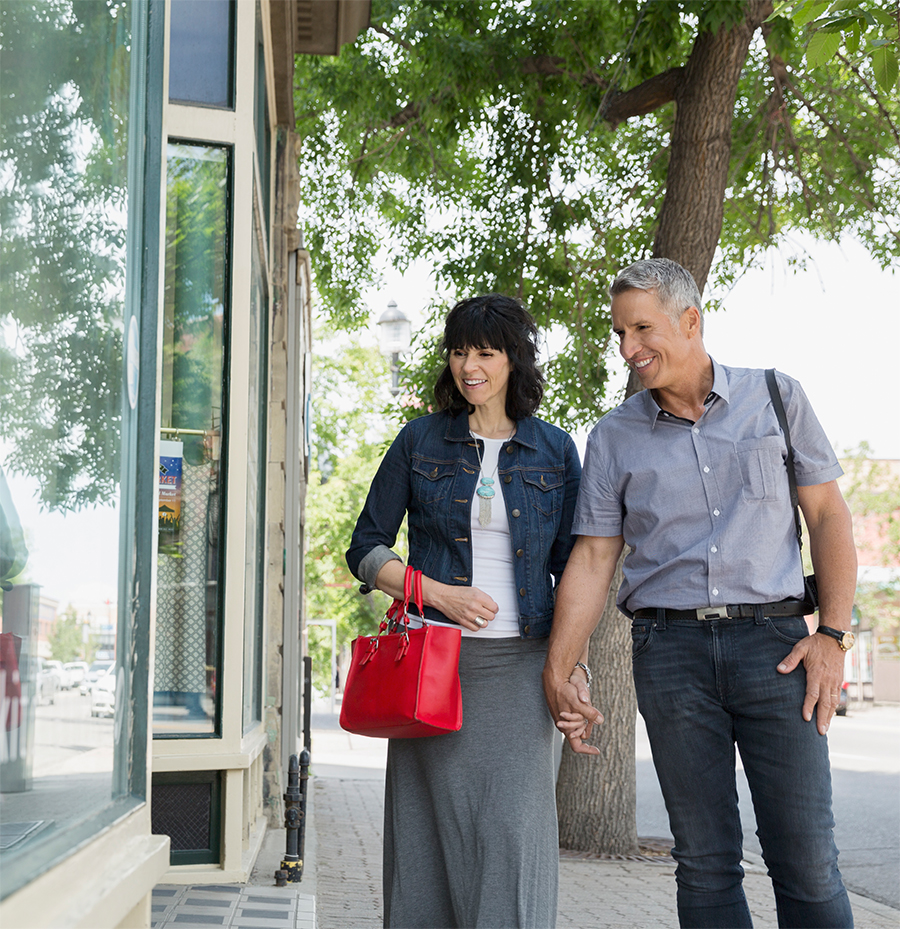Couple holding hands walking on sidewalk looking through shop windows